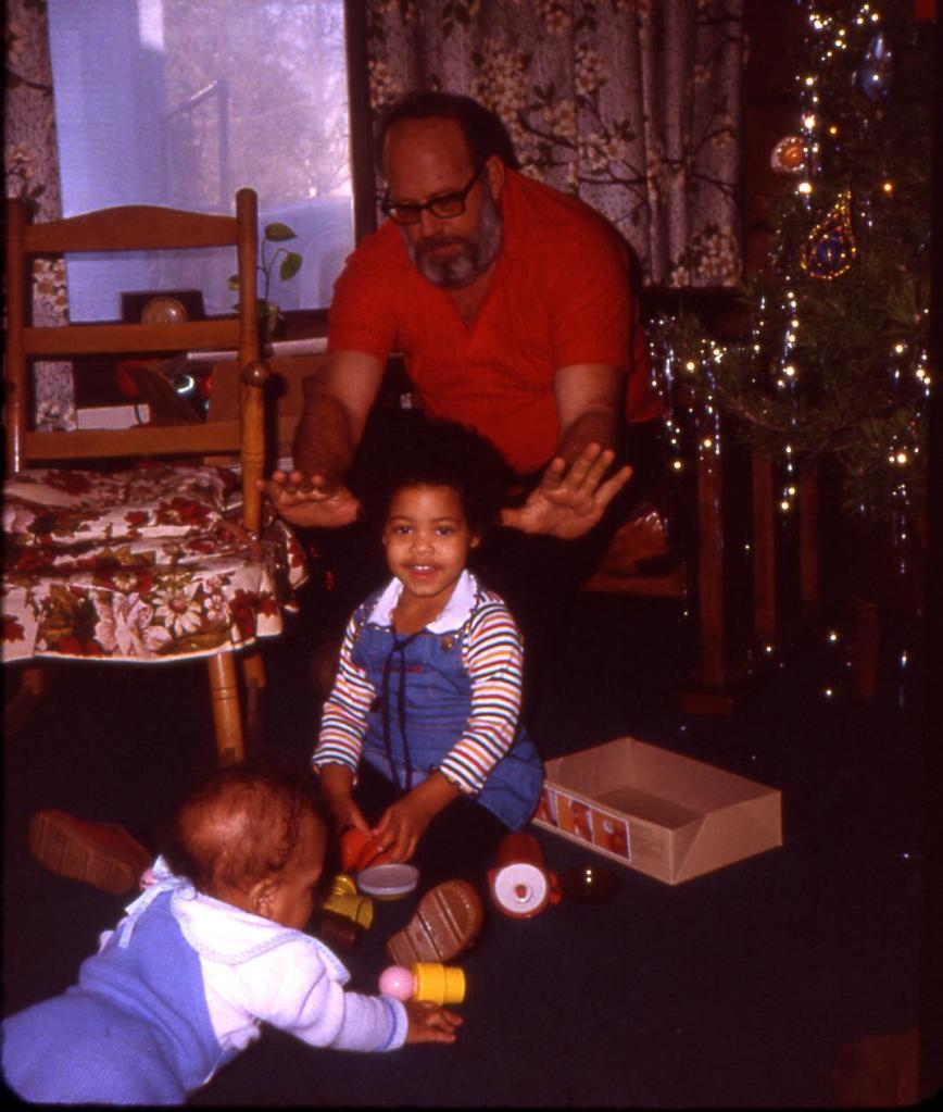Older Caucasian man sitting watching darker skinned toddler playing on the ground and baby lying down on front. All in front of a Christmas tree.