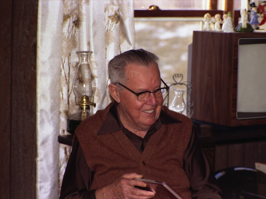 Older gentleman seated in a dark paneled room and in front of a window.