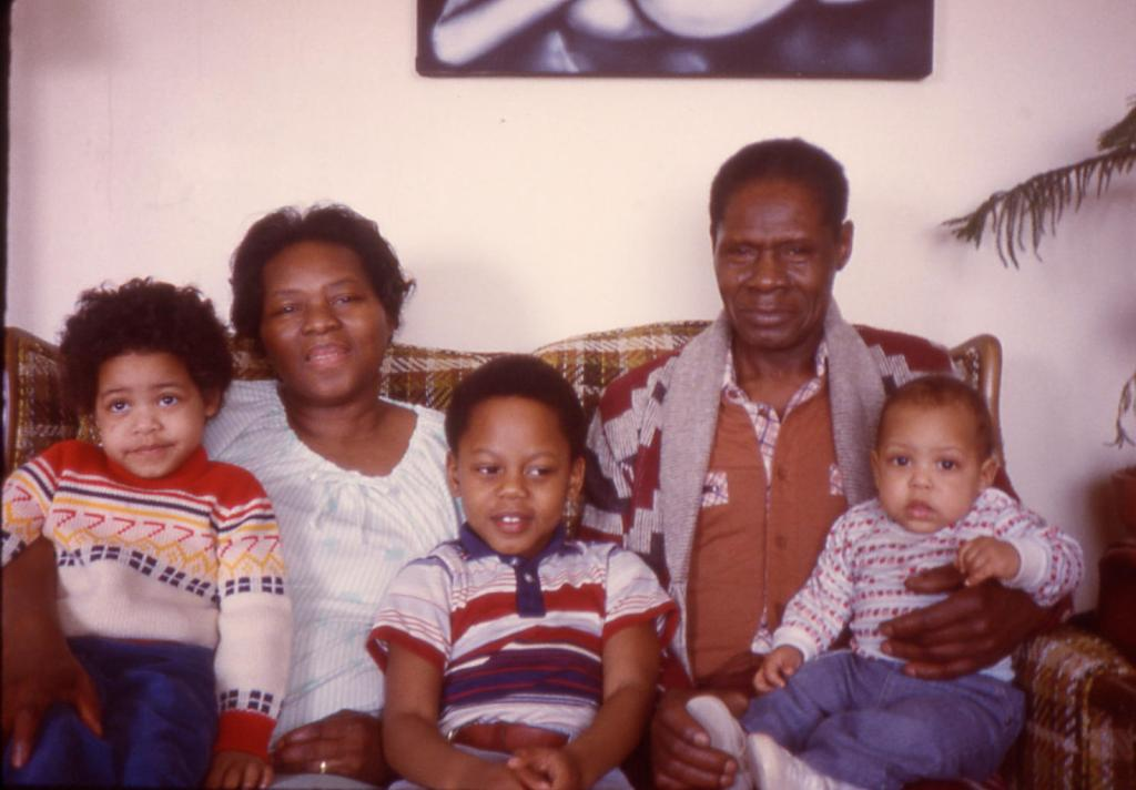 Older Black Couple sitting on a couch with 3 grandchildren--toddler, grade school age, and baby around 1979-1980.