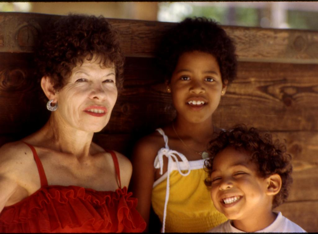 Older olive-complected woman and two darker skinned children, all dressed for summer.