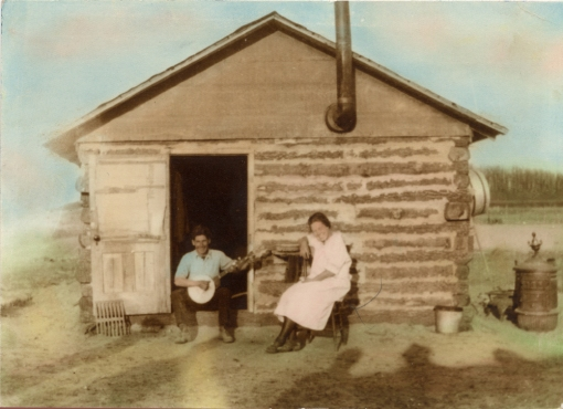 Robert Shea with a Banjo and Cora (Packer) Shea both seated in front of a log cabin.