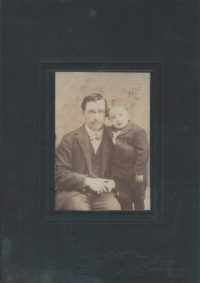 Black matted sepia photograph of Chapin Holden seated and young son Heman standing beside him. Facing the camera with head together.