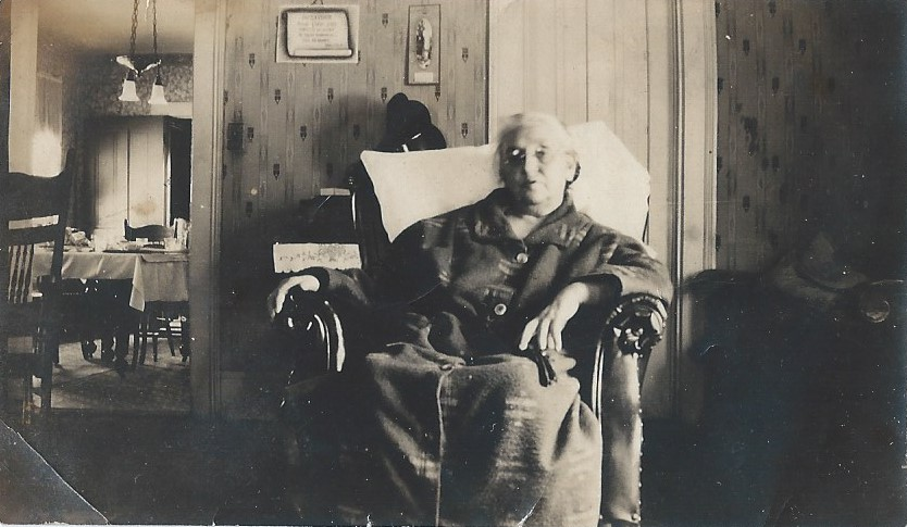 Sarah Porter seated in a chair in a living room.