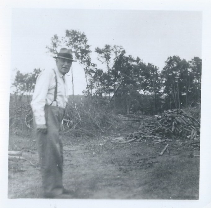 Black and white photograph of Charles Erwin Porter standing in field beside a large pile of chopped down trees.