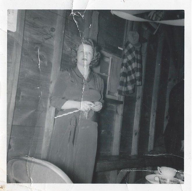 Black and white photograph of Crystal Porter standing in a rustic room with visible planks and studs.
