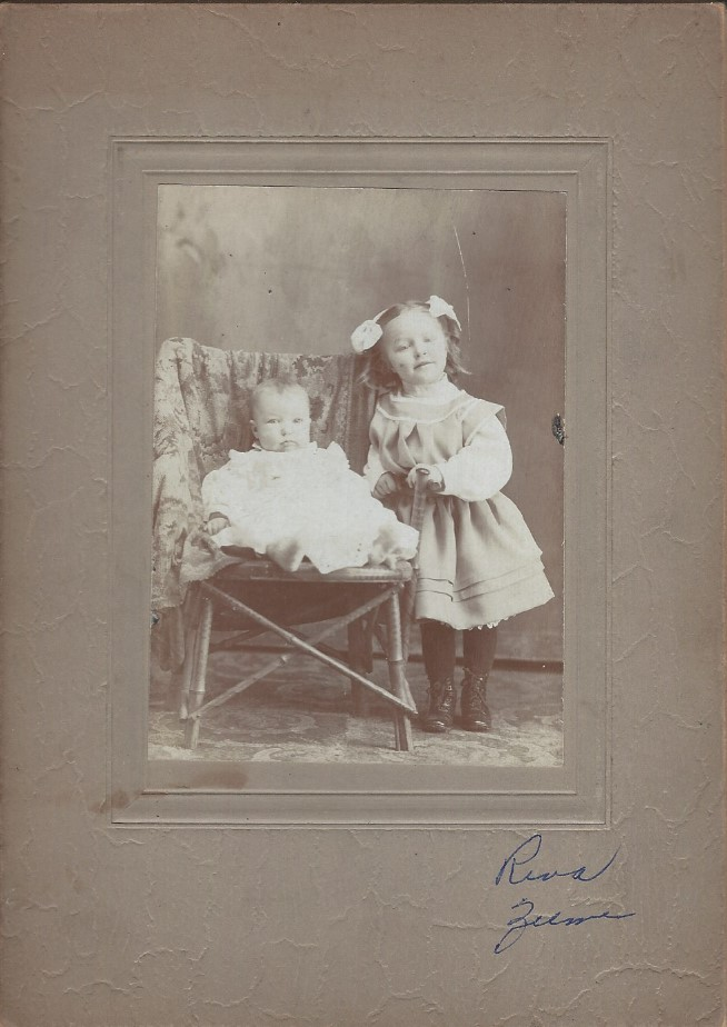 Photograph of Reva Porter as baby seated in a chair with sister Zelma standing beside the chair and leaning on the arm.
